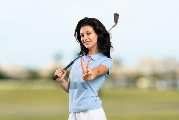 La giovane donna del giocatore di golf che sorride e che mostra la vittoria firma a all'aperto