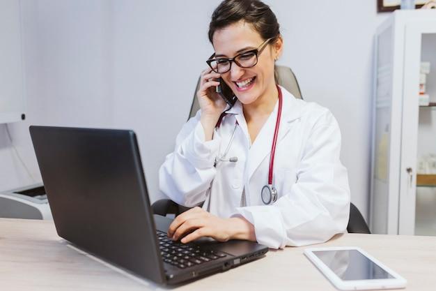 La giovane donna del medico che lavora al computer portatile al consulta. parlando sul cellulare. concetto medico moderno al chiuso