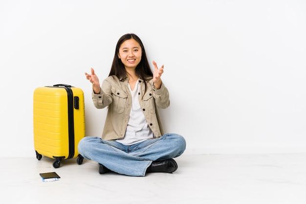 La giovane donna del viaggiatore che si siede tenendo i passaggi di imbarco si sente sicura dare un abbraccio alla macchina fotografica.