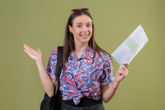 La giovane donna del viaggiatore con gli occhiali da sole rossi sulla testa e con la tenuta tiene lo zaino che sorride allegramente presentandosi con il braccio della mano sulla parete verde