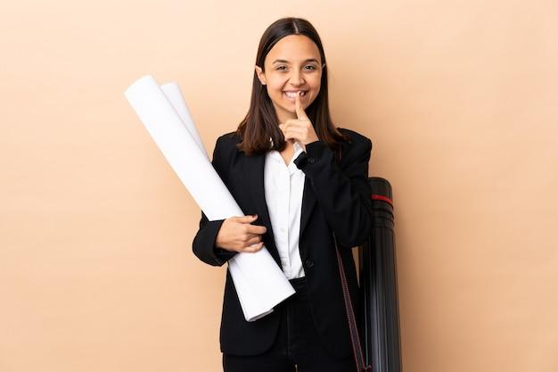 La giovane donna dell'architetto tiene i modelli sopra la parete che mostra un segno del gesto di silenzio che mette il dito in bocca