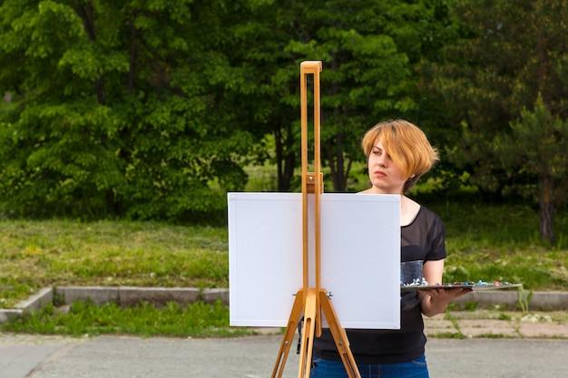 La giovane donna dell'artista dipinge su una tela un paesaggio urbano