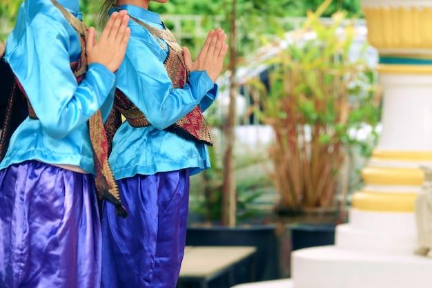 La giovane donna dell'asia che porta il vestito tradizionale della tailandia paga il rispetto