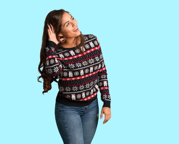 La giovane donna dell'ente completo che indossa una maglia di natale prova ad ascoltare un gossip