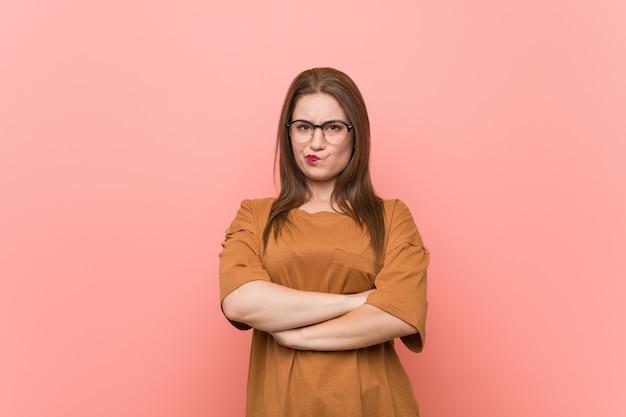 La giovane donna dello studente che indossa gli occhiali che aggrotta le sopracciglia nel disappunto, tiene le braccia conserte.