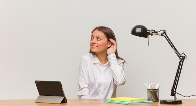 La giovane donna dello studente che lavora alla sua scrivania prova ad ascoltare un gossip