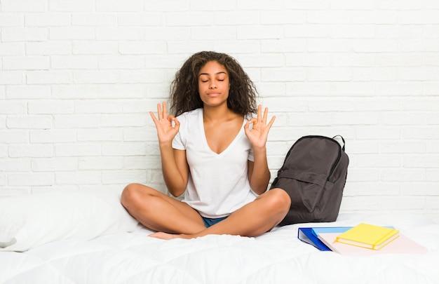 La giovane donna dello studente sul letto si rilassa dopo una dura giornata di lavoro, sta eseguendo yoga