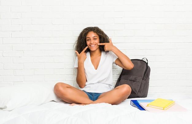 La giovane donna dello studente sul letto sorride, indicando le dita alla bocca
