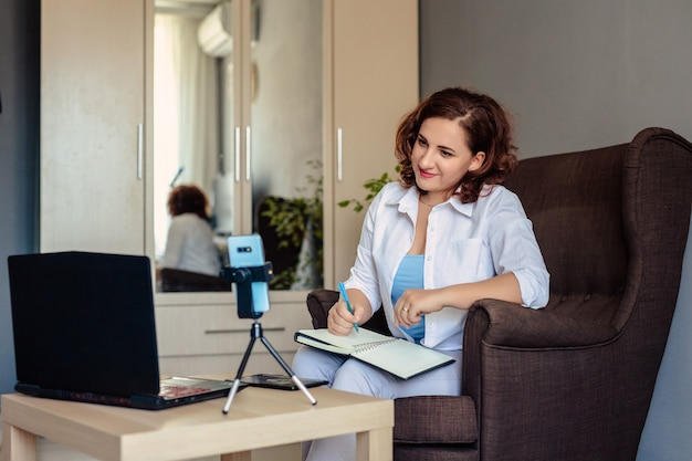 La giovane donna di 30 anni con una camicia bianca lavora nell'ufficio di casa e tiene una conferenza di formazione utilizzando videochiamate, il telefono è su un treppiede