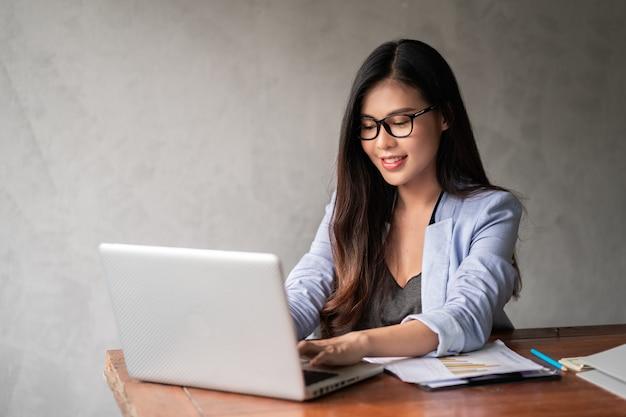 La giovane donna di affari asiatica felice in camicia blu che lavora dalla casa e usa un computer portatile del computer e pensa l'idea per il suo affare