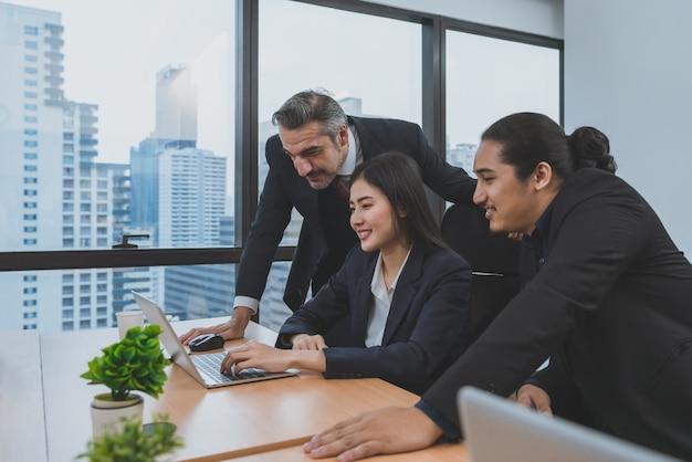 La giovane donna di affari asiatica presenta il suo lavoro sul computer portatile al senior manager e ai colleghi all'ufficio