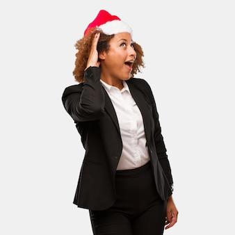 La giovane donna di affari che indossa un cappello di babbo natale di chirstmas prova ad ascoltare un gossip