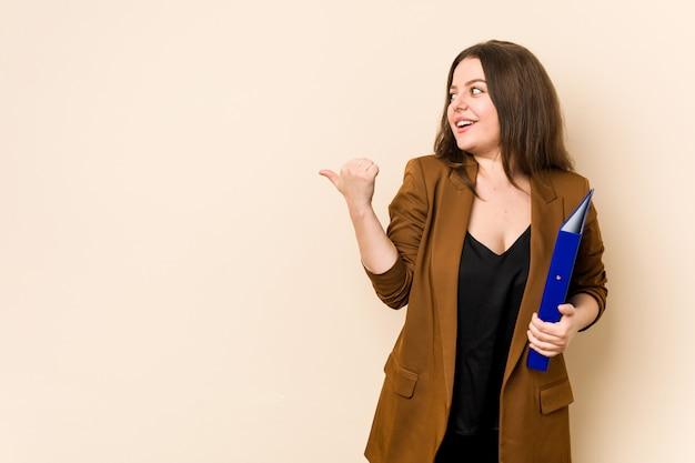 La giovane donna di affari che tiene gli archivi indica con il pollice via, ridendo e spensierato.