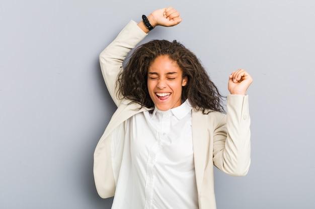 La giovane donna di affari dell'afroamericano che celebra un giorno speciale, salta e alza le braccia con energia.