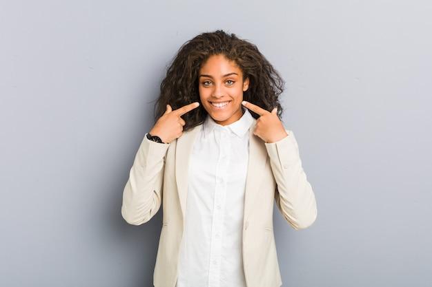 La giovane donna di affari dell'afroamericano sorride, indicando le dita alla bocca.