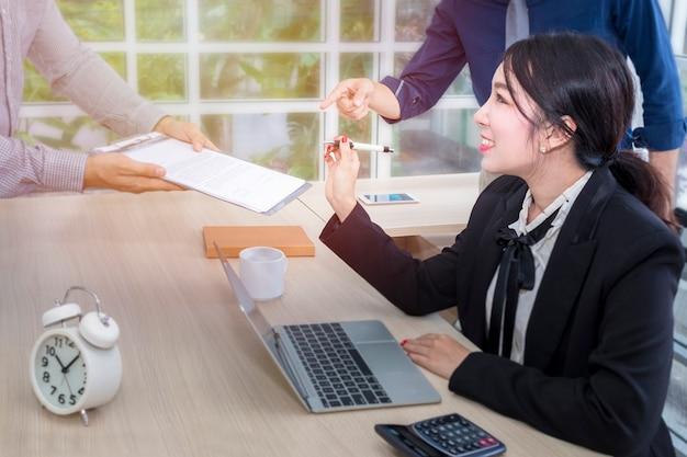 La giovane donna di affari firma un documento e una riunione con il lavoro di squadra di affari all'ufficio.
