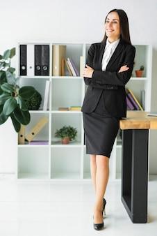 La giovane donna di affari sorridente con le sue braccia ha attraversato distogliere lo sguardo