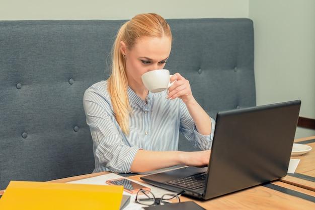 La giovane donna di affari sta bevendo il caffè mentre utilizzava il computer portatile all'ufficio