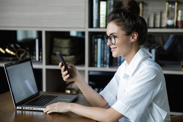 La giovane donna di affari sta parlando dallo smartphone