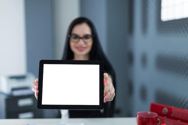 La giovane donna di affari sveglia in vestito e vetri neri si siede alla tavola e mostra la compressa vuota