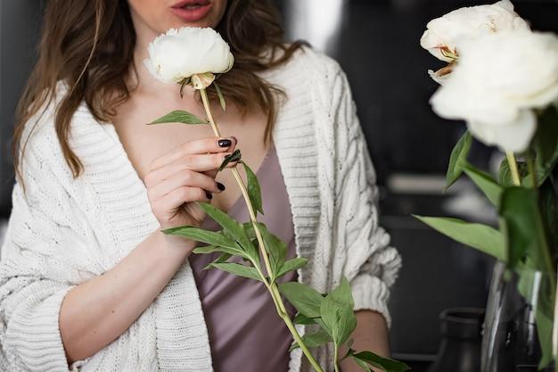 La giovane donna di attractine fa un mazzo di peonie bianche in un vaso
