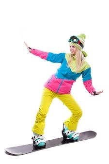 La giovane donna di bellezza in vestito di sci e vetri di sci guida lo snowboard