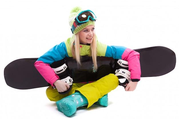 La giovane donna di bellezza in vestito di sci e vetri di sci si siede con lo sbowboard