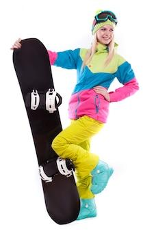 La giovane donna di bellezza in vestito di sci e vetri di sci tiene lo snowboard