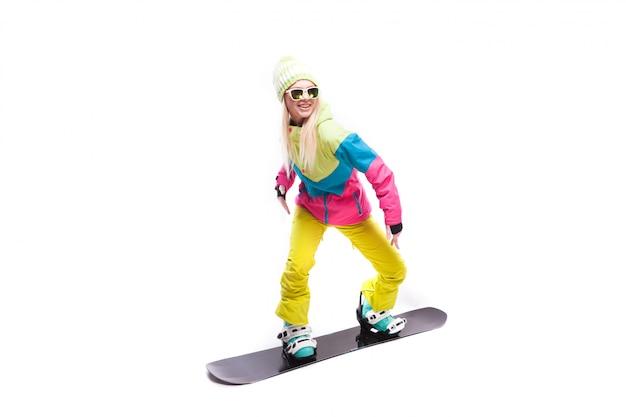 La giovane donna di bellezza in vestito e occhiali da sole dello sci guida lo snowboard