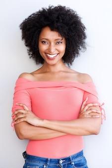 La giovane donna di colore attraente che sta con le armi ha attraversato e sorridente contro fondo bianco