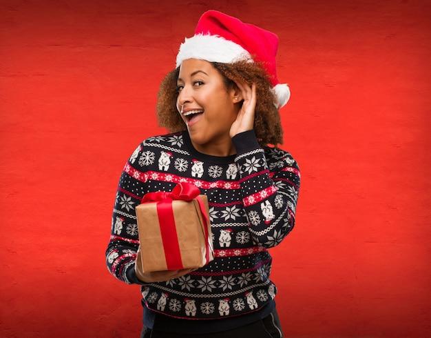 La giovane donna di colore che tiene un regalo in giorno di natale prova ad ascoltare un gossip