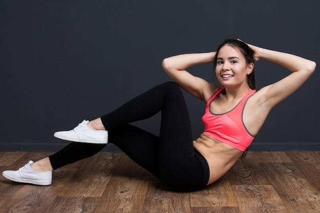 La giovane donna di forma fisica allena i muscoli addominali e sorridere