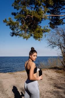 La giovane donna di forma fisica cammina nel parco e nella posa per la macchina fotografica