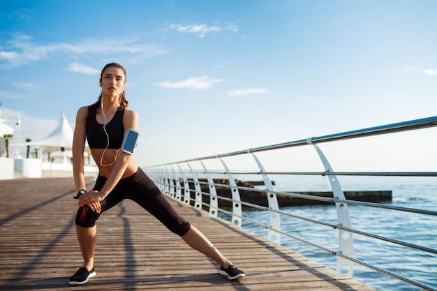 La giovane donna di forma fisica che fa gli esercizi di sport con la costa di mare dietro