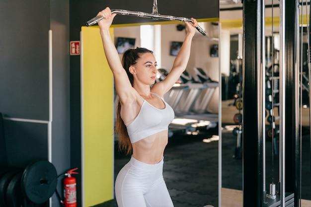 La giovane donna di forma fisica esegue l'esercizio con la macchina di esercizio in palestra.