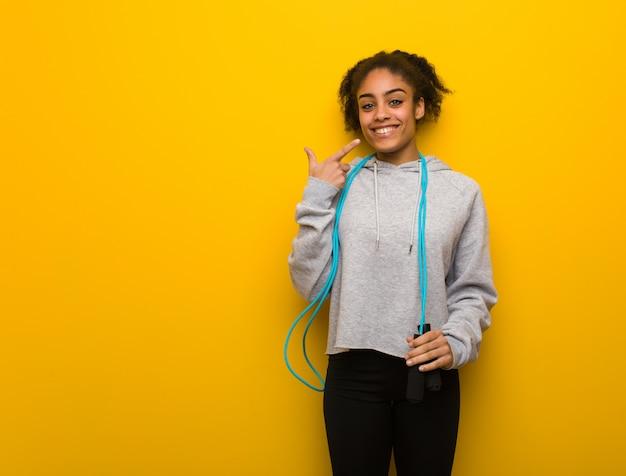 La giovane donna di forma fisica sorride, indicando la bocca. tenendo una corda per saltare.