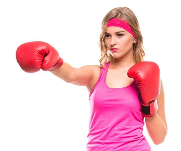 La giovane donna di forma fisica sta indossando i guantoni da pugile.
