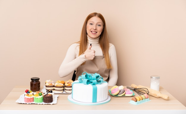 La giovane donna di redhead con una grande torta che dà un pollice in su gesto