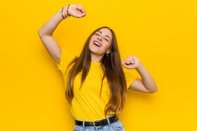 La giovane donna di redhead dello zenzero che celebra un giorno speciale, salta e alza le braccia con energia.