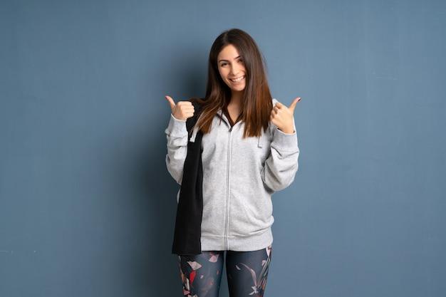 La giovane donna di sport che dà un pollice aumenta il gesto e sorridere