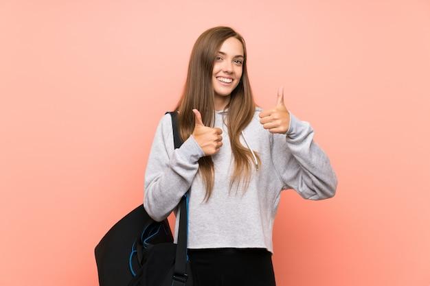 La giovane donna di sport che dà un pollice aumenta il gesto