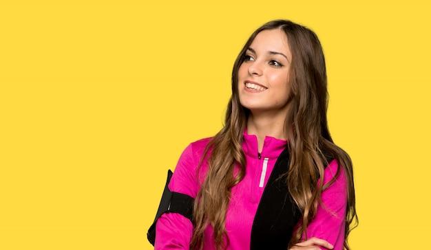 La giovane donna di sport che tiene le armi ha attraversato mentre sorrideva sopra la parete gialla isolata