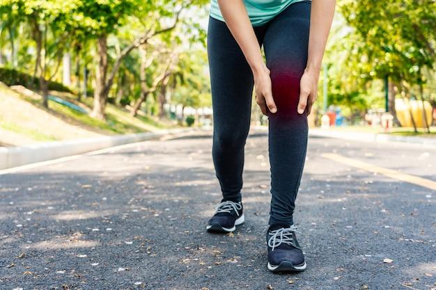 La giovane donna di sport tiene il suo ginocchio danneggiato dentro all'aperto.