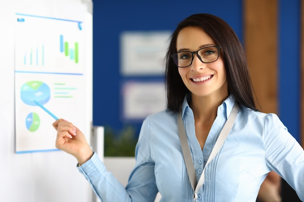 La giovane donna di successo in vetri tiene la conferenza