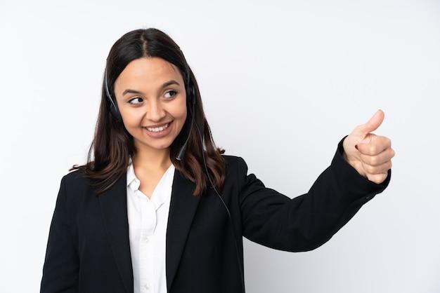La giovane donna di telemarketer isolata su bianco dando pollici aumenta il gesto