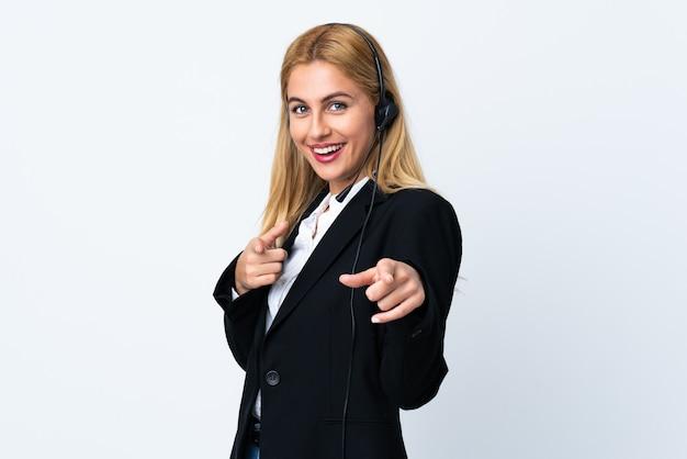 La giovane donna di telemarketer sopra il bianco isolato indica il dito con un'espressione sicura