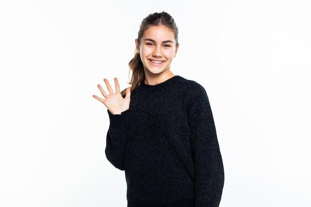 La giovane donna dice ciao isolato sulla parete bianca