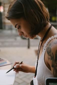 La giovane donna disegna allo sketchbook con una matita all'aperto sulla strada