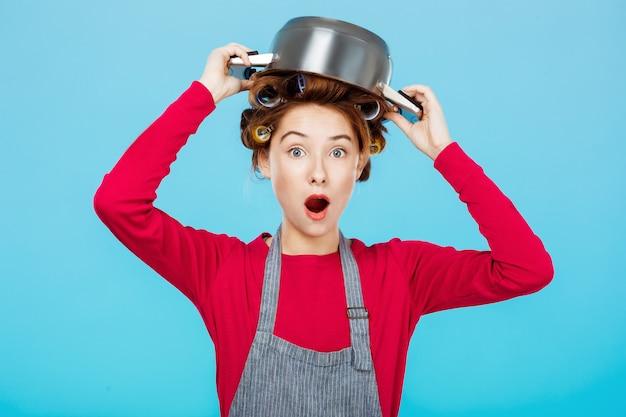 La giovane donna divertente posa con soucepan sulla testa