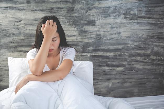 La giovane donna è depressa su un letto bianco